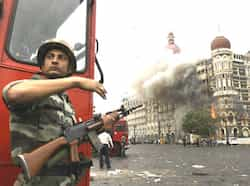 A soldier takes cover as the Taj Mahal hotel burns during gun battle between military and militants inside the hotel in Mumbai. 26/11 Mumbai attacks