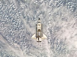 In this image provided by NASA Space Shuttle Endeavour is backdropped by a cloud-covered part of Earth in this image photographed by an Expedition 18 crewmember Friday November 28, 2008. Melange