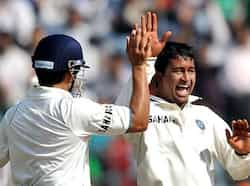 Pragyan Ojha (R) celebrates with teammate Gautam Gambhir after taking the wicket of West Indies batsman Darren Bravo during fifth day