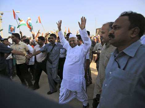 Anti-corruption activist Anna Hazare (C) waves to supporters as he arrives to pay homage at a memorial for Mahatma Gandhi in Mumbai. Anna in Mumbai