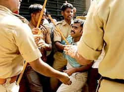A man is taken out of a crowd by policemen from the queue for tickets of the India and England Group B cricket World Cup match at the M Chinnaswamy Stadium in Bangalore. Ticket chaos in Bangalore