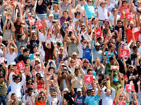 Spectators in the Compton stand raise their arms during a Mexican wave during the final day of the first cricket Test match between England and India at Lord