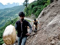 Indian residents carry a jerry-can as they cross a landslide at Phengla on the outskirts of Gangtok. 6.8 quake: Rescue operation