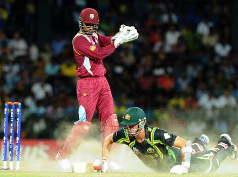 Australian cricketer Pat Cummins runs between the wickets as West Indies cricketer Samuel Badree as West Indies wicketkeeper Denesh Ramdin (L) looks on during the ICC Twenty20 Cricket World Cup
