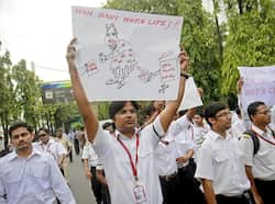 An employee holds a poster with an illustration of Vijay Mallya, chairman and chief executive of Kingfisher Airlines, during a protest march against the company in Mumbai. Reuters An act of solidarity