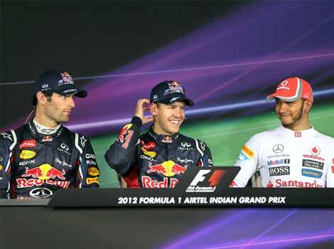Red Bull driver Sebastian Vettel, centre, of Germany smiles as he sits with teammate Mark Webber of Australia at a press conference following his win in the qualifying session for the Indian Formula One Grand Prix at the Buddh International Circuit in Noida, on the outskirts of New Delhi.  AP Photo Indian GP: Vettel takes pole