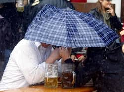 Oktoberfest visitors sit under an umbrella during heavy rain at the last day of the world biggest beer festival in Munich. Reuters Photo Millions of pints later
