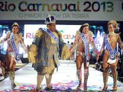 Brazilian Milton Junior performs as King Momo followed by the Queen of 2013 Carnival Evelyn da Silva and Princess lara de Oliveira and Leticia Guimaraes during the Carnival