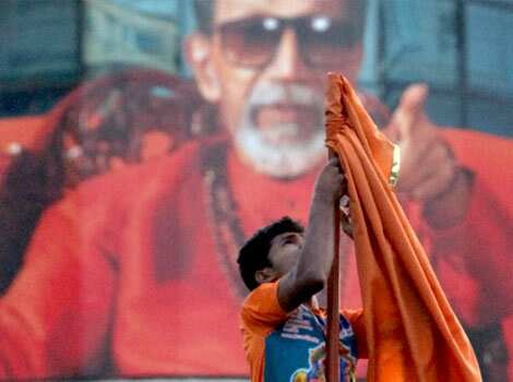 A Shiv Sena worker removes the party flag from the Sena Bhavan after the news of Balasaheb Thackeray