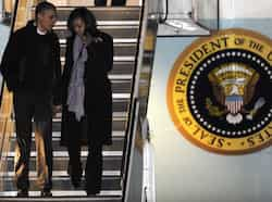 President Barack Obama and first lady Michelle Obama walk off Air Force One after arriving at O