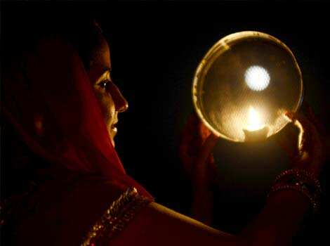 A Hindu woman poses while performing a ritual on the occasion of the festival of Karva Chauth in Amritsar . Married women observe Karvachauth by fasting and offering prayers seeking welfare, prosperity, and longevity of their husbands. AFP Photo/ Narinder Nanu Happy Karva Chauth!