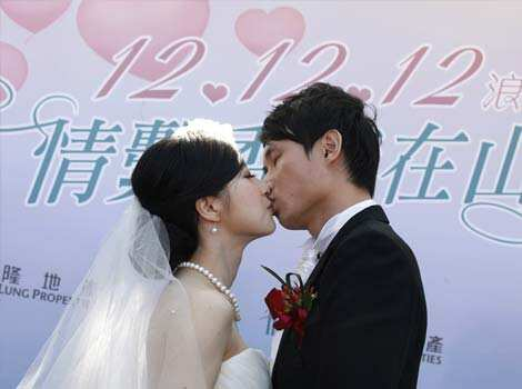 A couple kiss during a mass wedding ceremony at the Peak in Hong Kong. At least 700 couples are expected to get married in the date 12/12/12, the last such triple-date in this year in Hong Kong as they believe the date will bring them everlasting love.  (AP Photo) Wedding vows on 12.12.12