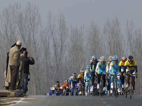 People watch a peloton of riders cycle past them during the second leg of the Tour de India cycling race in Srinagar.It is the first ever international cycling race held in India. Reuters Tour de India