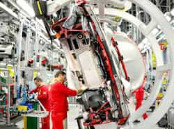 Employess work on Ferrari tourism cars held on pincers on the assembly line of the Ferrari factory in Maranello. AFP Photo Making of speed machines