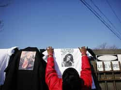 Woman hangs T-shirts of late singer Whitney Houston for sale during her funeral service in Newark. (Reuters/Eduardo Munoz) Farewell Whitney