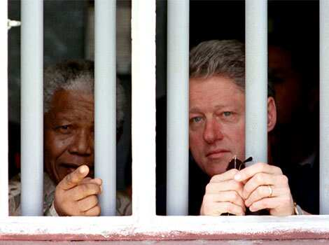 File photo: US President Bill Clinton and South African President Nelson Mandela peer through the bars of the cell in which Mandela spent 17 years while incarcerated by the former South African government. Reuters Nelson Mandela: world icon