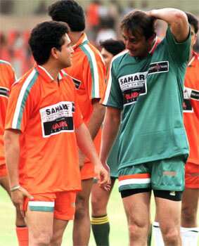 Sachin Tendulkar (L) talks with Bollywood star Sanjay Dutt during a charity football match pitting Indian cricket stars against India