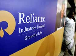 A woman walks past a poster of Reliance Industries installed outside the venue of the company