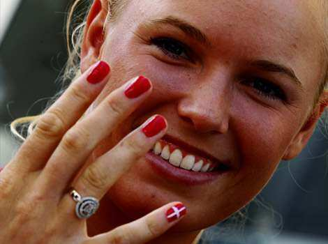 Caroline Wozniacki of Denmark displays her fingernails decorated with her national flag as she arrives during the Olympic Village arrivals ahead of the London 2012 Olympics at the Olympic Park in London. Reuters/Alexander Hassenstein/Pool Patriotic polish!