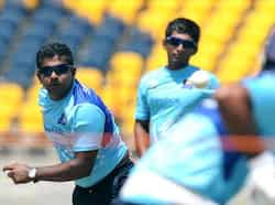 Sri Lanka cricketer Rangana Herath (L) delivers a ball during a practise session at the Suriyawewa Mahinda Rajapakse International Cricket Stadium in the southern district of Hambantota. AFP Photo/Ishara S. Kodikara Hambantota practise session