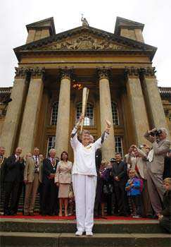 This image made available by LOCOG shows torchbearer 098 Patricia Pearce MBE carrying the Olympic Flame outside Blenheim Palace on the Torch Relay leg between Bicester and Woodstock, England. AP/Chris Radburn, LOCOG Olympic torch bearers