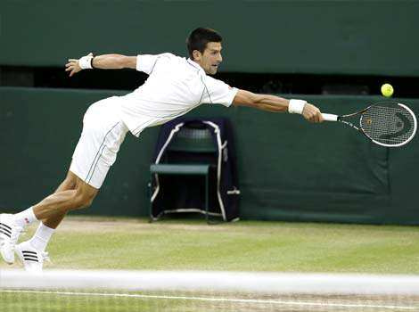 Novak Djokovic of Serbia plays a shot to Roger Federer of Switzerland during a men
