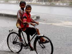 Two youngsters riding a cycle pedal through a downpour in Amritsar on Saturday. (Avneet/ HT photo) Region in pics