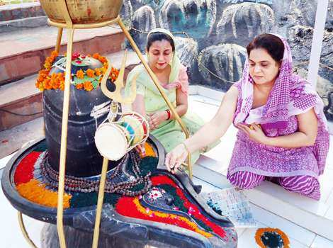 Women decorating a shivling at Mahalakshmi temple in Jalandhar on Wednesday. (Pardeep Pandit/HT) Region in pics