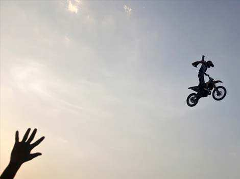 A member of the audience waves at a rider performing a stunt during the Red Bull X-Fighters freestyle motocross motorbike event at India Gate in New Delhi. Reuters/Ahmad Masood