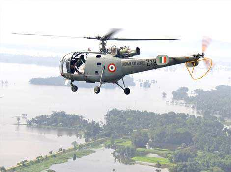An Indian Air Force (IAF) helicopter, carrying relief supplies, flies over the flooded areas of the Sonitpur district, Assam. Reuters/Stringer Flood-hit Assam