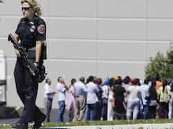 Police stand guard as bystanders watch at the scene of a shooting inside a Sikh temple in Oak Creek. (AP Photo) US gurudwara shooting kills 7