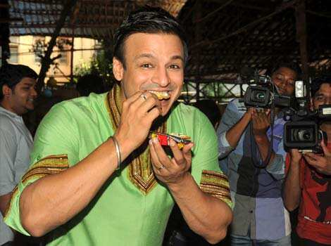 Vivek savours street food as the cameras click on. Mallika, Vivek get naughty at KLPD promotions
