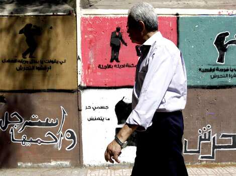 "A man walks past anti-sexual harassment graffiti along Mohamed Mahmoud Street near Tahrir Square in Cairo. The Arabic words read, ""No harassment - Be man and protect her"". Reuters/Amr Abdallah Dalsh Cairo clash graffiti"