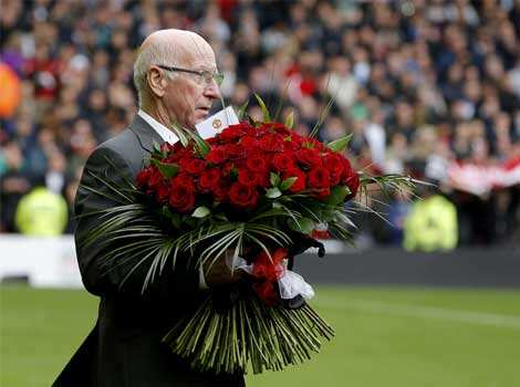 Former Manchester United player Bobby Charlton holds 96 red roses in memory of the victims of the Hillsborough disaster before the English Premier League soccer match between Liverpool and Manchester United at Anfield in Liverpool. The fixture is Liverpool