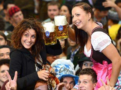Visitors of the Oktoberfest raise their beers in a festival tent at the start of the Oktoberfest beer festival at the Theresienwiese in Munich, southern Germany. AFP PHOTO / CHRISTOF STACHE Raising the beer