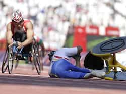 Jesus Aguilar of Venezuela falls from his wheelchair as he crashes out of a men