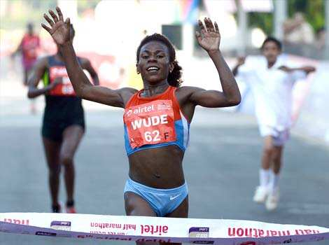 Yimer Wude celebrates as she crosses the finishing line to claim victory in the women