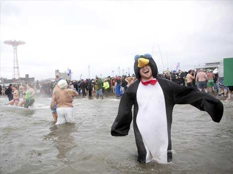 A man dressed as a penguin enters the water while taking part in the Coney Island Polar Bear Club