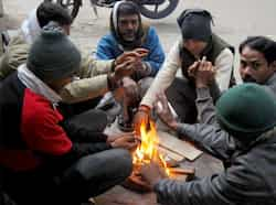 People warm themselves around a small fire on a cold day in New Delhi as maximum temperature dropped to to 9.8 deg Celsius, the lowest in 44 years. UNI It