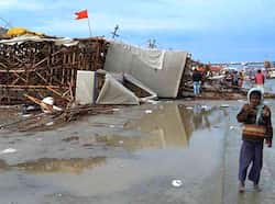 People walk past a pandal which fell down in heavy rains at Kumbh Mela in Allahabad. PTI Rain lashes north India