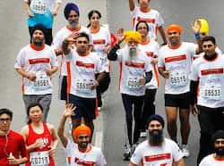 Marathon runner Fauja Singh, 101, center, originally from Beas Pind, in Jalandhar, now living in London, runs in a 10-kilometer race, part of the annual Hong Kong Marathon. AP photo Fauja Singh