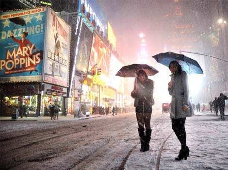 Two girls look for a taxi in the snow in Times Square in New York during a storm affecting the northeast US. AFP Snowed in!