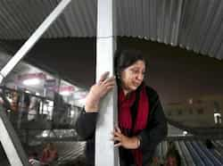 A woman weeps as she watches from a staircase as rescue workers tend to the bodies of those killed in a stampede on a railway platform in Allahabad (AP Photo) Stampede in Allahabad