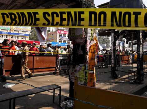 People gather at one of the two bomb blast sites in Hyderabad. As the suspect