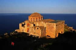 A Belgian tourist walks atop the medieval fortress of Monemvasia in front of the 12th century church of Agia Sophia. Reuters/Yannis Behrakis Greece