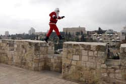 A Palestinian man dressed up in a Santa Claus costume walks on Jerusalem