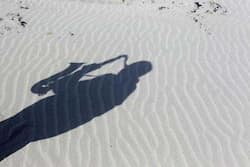 The shadow of artist and poet Barry Edgar Pilcher, age 69, is cast on the sand as he plays the saxaphone on the Island of Inishfree in County Donegal. Photo: Reuters/Cathal McNaughton  One man island