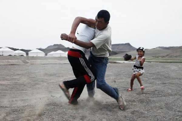 Men wrestle as a girl reacts at a tourist camp near the ruins of Ongi monastery in Mongolia