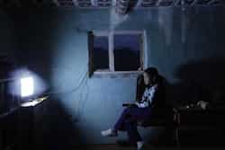 A Mongolian girl watches television in a house at a tourist campsite in Mongolia